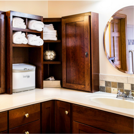 Dark wood bathroom cabinets with white towels and countertops