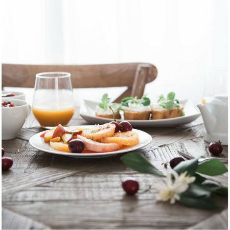 Orange juice and plated fruit on a table