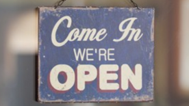 Come In We're Open sign hanging on a window