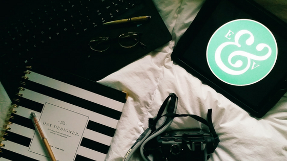 Elle & Vine Logo on an iPad, laptop, day planner, gold pens, and a camera on a white down comforter