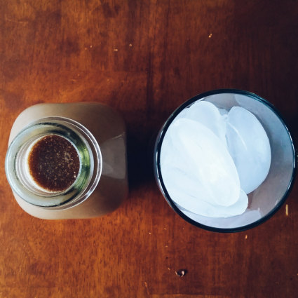 A glass milk bottle filled with Chai Latte and a glass of ice