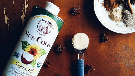 A bottle of Latourangelle SunCoco Organic Oil, a tablespoon of grassfed butter, spices, and whole star anise