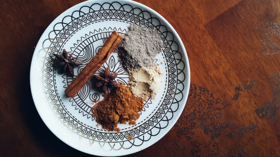 Whole star anise, cinnamon stick, groung cinnamon, ground ginger, and ground cardamom on a decorative plate